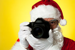 Aged Santa adjusting camera lens before click Royalty Free Stock Photos