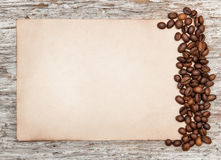 Aged sheet of paper with coffee beans on the old wood Royalty Free Stock Photo