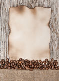 Aged sheet of paper with coffee beans on the old wood Stock Images