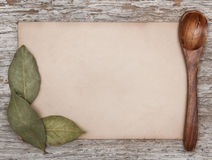 Aged sheet of paper, wooden spoon and dry bay leaves Royalty Free Stock Photo