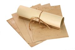 Aged sheets and scroll. Aged sheets of paper and a scroll lying on them Royalty Free Stock Photography