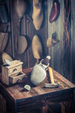 Aged shoemaker workplace with brush and shoes Stock Photography