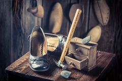Aged shoemaker workplace with shoes, hammer and nails royalty free stock image