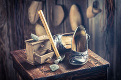 Aged shoemaker workplace with tools, leather and shoes. On old wooden table royalty free stock photography