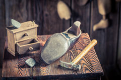 Aged shoemaker workplace with tools, shoes and laces stock image