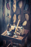 Aged shoemaker workplace with tools, shoes and leather Stock Photography
