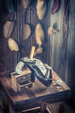 Aged shoemaker workshop with tools, leather and shoes Royalty Free Stock Photo