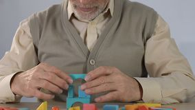 Aged sick man doing well in making house of wooden figures, dementia therapy. Stock footage stock video footage