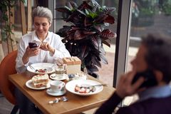 Aged smiling woman in cafe checking smartphone. Enjoyable meetings. Waist up portrait of smiling elegant aged lady checking mobile phone while having dinner with royalty free stock photo