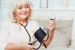 Aged smiling woman measuring blood pressure Royalty Free Stock Photo