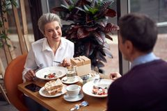 Aged smiling woman meeting with man in cafe. Enjoyable meetings. Waist up top angle portrait of pleased smiling aged lady eating salad while having dinner with stock image