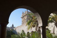 Spanish architecture. View through the arches of the palace. on palms garden in a sunny day stock photography