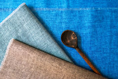 Aged spoon on kitchen linen napkins stock images