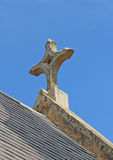 The aged stone cross of a church in a bright blue sky Royalty Free Stock Photo