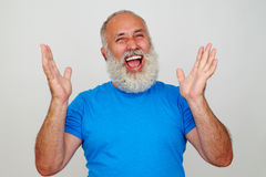 Aged stylish man laughing sincerely with hands lifted Stock Images