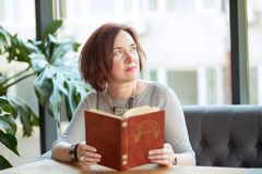 Aged stylish woman with a book daydreaming royalty free stock images