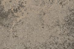 Weathered textured gray surface of the artificial stone. Aged surface of artificial stone made of mixture of mortar and small white marble pieces. Gray dirty old royalty free stock photo