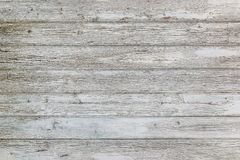 Aged surface of horizontal wooden planks with cracked white paint. Peeling paint on an old wooden wall stock photo