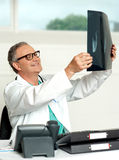 Aged surgeon holding patients x-ray report. And reviewing it. Sitting in his clinic Stock Image