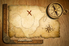 Aged treasure map, ruler and old brass compass. On wooden table t stock photos