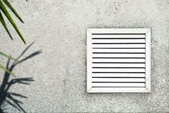 Aged vent with white shutters on the background of gray concrete under leaves of the palm. Aged vent with white shutters on the background of gray concrete royalty free stock photography