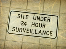 Aged vintage surveillance sign Stock Photos