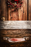 Aged vintage wooden suitcase at rustic background with Christmas wreath Stock Images