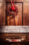 Aged vintage wooden suitcase at rustic background with Christmas wreath. Royalty Free Stock Photography