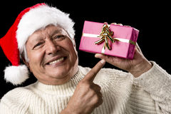 Aged, But Vivid Gentleman Pointing At Wrapped Gift. Male pensioner radiant with happiness in white pullover and red Santa Claus cap. He is reminding us of gift Royalty Free Stock Photography