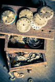 Aged watchmaker's workshop with damaged clocks Stock Image
