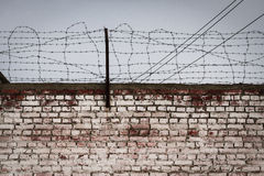 Aged and weathered brickwall with a barbed wire. Aged brick wall and a barbed wire Royalty Free Stock Image