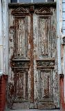 Aged weathered wooden entrance doors with peeling paint Royalty Free Stock Photo