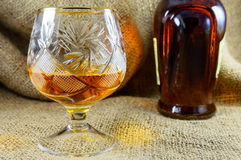 Aged whiskey in a crystal glass beside the bottle Royalty Free Stock Photos