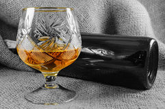 Aged whiskey in a crystal glass next to the bottle Royalty Free Stock Photos