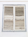 Aged white closed window shutters with peeling paint Royalty Free Stock Photos