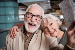 Aged wife and husband are expressing gladness at international airport. Happy journey. Portrait of delighted old romantic couple is standing at modern terminal stock images