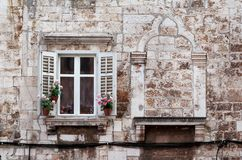 Aged windows and flower boxes of historical building from old town of Pula, Croatia / Detail of ancient venetian architecture. Aged windows and flower boxes of Royalty Free Stock Image