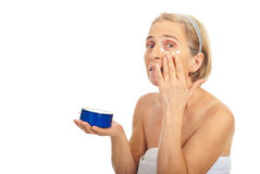 Aged woman apply cream around eye Royalty Free Stock Photo