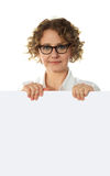 Aged woman behind big blank white banner ad. Looking right into camera Royalty Free Stock Photography