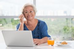 Aged woman. Calling on the phone while working on her computer Stock Photography