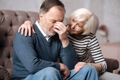 Aged woman calming down her depressed husband Stock Image