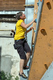 Aged Woman Climbing Wall Stock Photo
