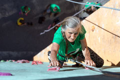 Aged Woman Climbing Wall Royalty Free Stock Image