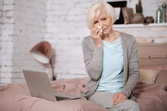 Aged woman crying while sitting on bed. Very bad news. Portrait of sad senior woman sitting on bed and wiping nose with napkin Stock Image