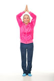 Aged woman doing yoga royalty free stock photography
