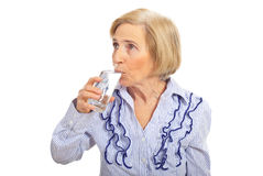 Aged woman drinking glass of water Stock Images