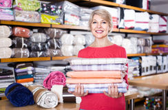 Aged woman enjoying purchased home textiles in textile shop Stock Photos