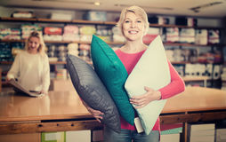 Aged woman enjoying purchased home textiles in textile shop Royalty Free Stock Photos