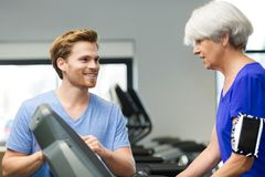 Aged woman exercising with fitness instructor in gym Royalty Free Stock Images