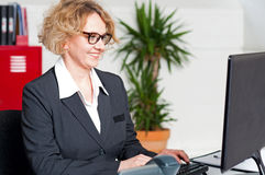 Aged woman in eyeglasses working on computer Royalty Free Stock Photography